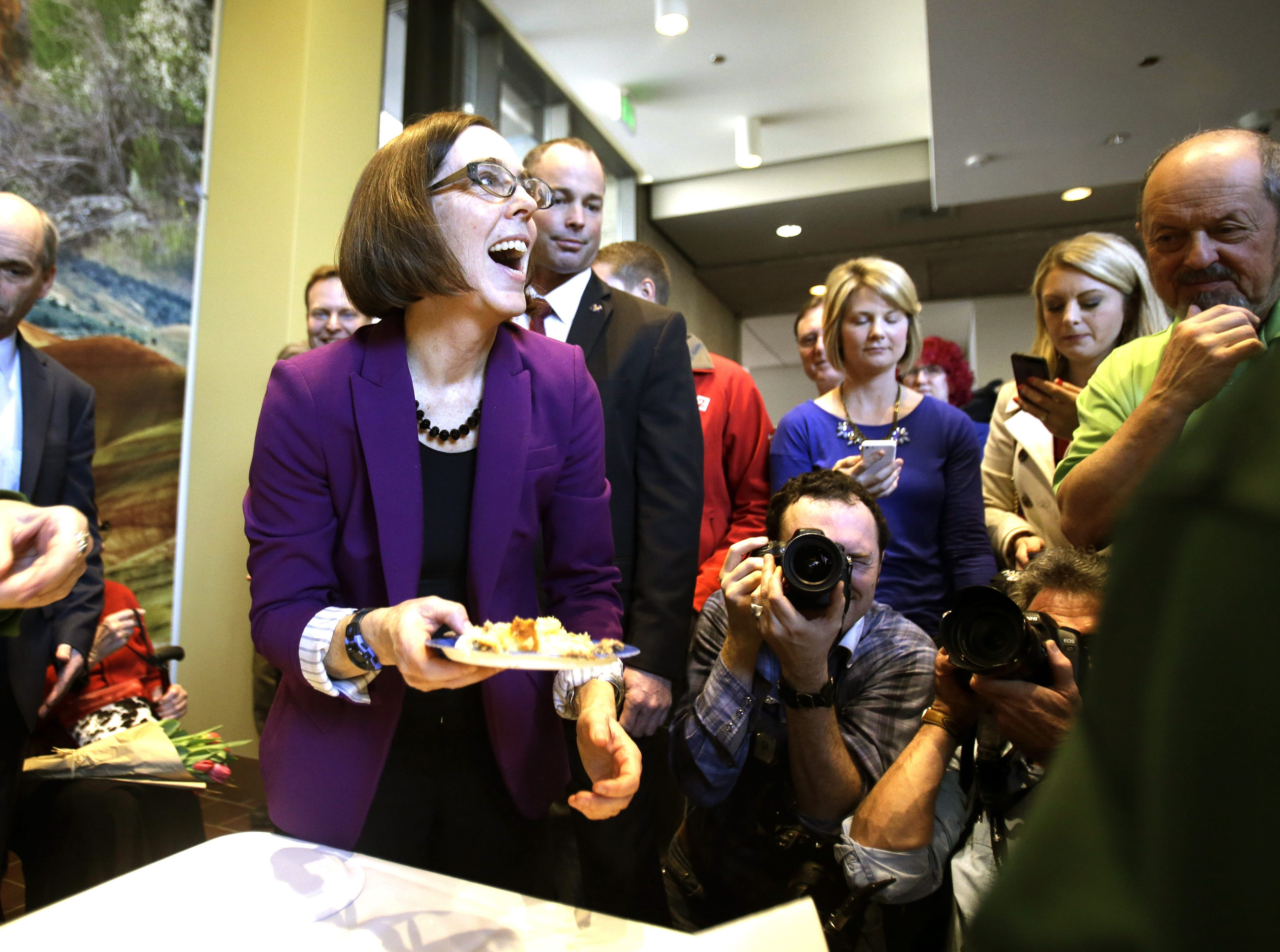 Oregon Secretary of State Kate Brown, a week before taking over as governor, serves up cake on Feb. 14, 2015, during a celebration at the Oregon Historical Society to mark the 156th anniversary of Oregon's admission to the union as the 33rd state.