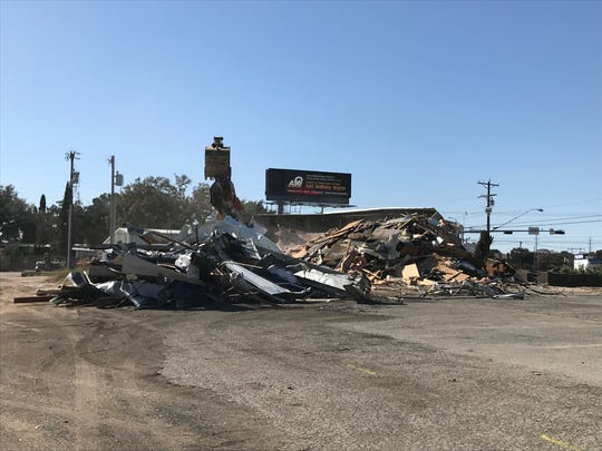 Large piles of the former Cork & Pig Tavern, 2201 Knickerbocker Road wait to be cleared away on Tuesday, Feb. 12. The second Firestone Complete Auto Care will open here.