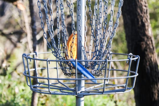 Discs in a basket used for disc golf.