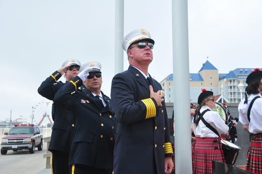 In this file photo, Ocean City Fire Department Chief Chris Larmore pays his respects during the Pledge of Allegiance while participating in the Ocean City Fire Department 9/11 Memorial at the Firefighters Memorial on the Boardwalk at North Division Street.