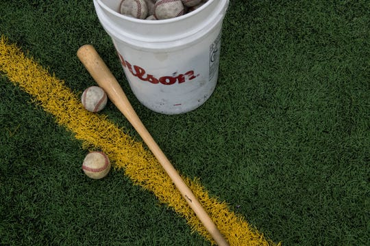 Baseballs and a bat lay on the ground during Augustana baseball practice at the Sanford Fieldhouse in Sioux Falls, S.D., Wednesday, Feb. 13, 2019.