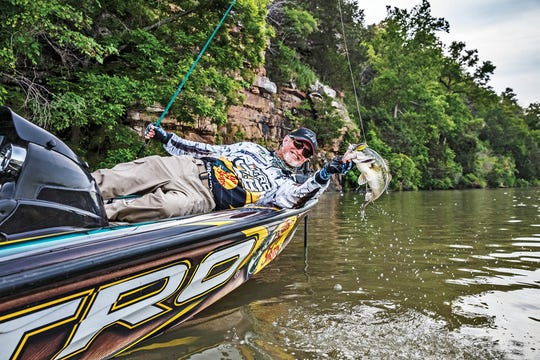Rick Clunn hauls in another largemouth bass. The angler from Ava has been fishing professionally for more than 30 years.