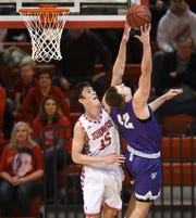 Lucas Walford leaps to block a shot during the Wednesday, Feb. 13, game against St. Thomas in Collegeville.