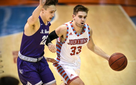 Sean Ryan advances with the ball for St. John's during the Wednesday, Feb. 13, game against St. Thomas in Collegeville.