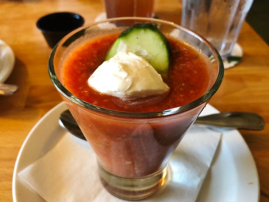 The Cottage Grill gazpacho was a cup of cold, spicy, tomato broth and vegetables were garnished with sour cream and a slice of cucumber.