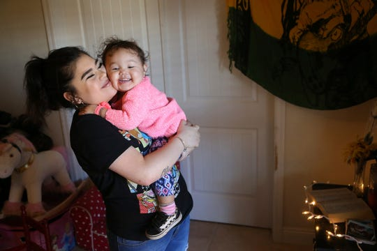 Seanna Leilani Chavez, left, the sister of Aaron Francisco Chavez, holds Athena Chavez, 2, his daughter, as the two stand next to a shrine for Aaron at the family home Wednesday, Feb. 6, 2019, in Tucson, Ariz. Aaron Chavez died of a fentanyl overdose at the age of 19.