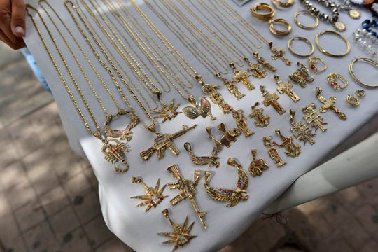 "In this July 22, 2015, file photo, a man sells jewelry, many of it with narco-culture imagery, in downtown Culiacan, Mexico. U.S. officials hailed the conviction of Joaquin ""El Chapo"" Guzman as a victory for the Mexican people, but in the drug lord's home state of Sinaloa, cradle to his powerful cartel, many residents said they don't expect the violence and trafficking to abate."