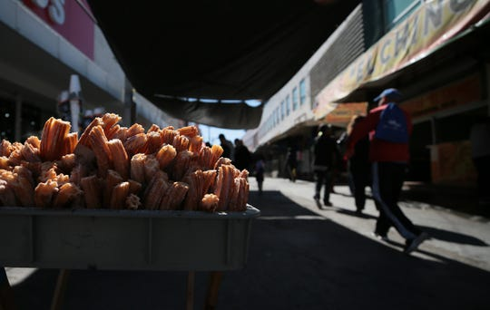 Juarenses stroll through the Mercado Reforma in downtown Juarez past a cart selling churros on Tuesday, February 12, 2019. Life has returned to the streets of the embattled city after years of cartel killings.