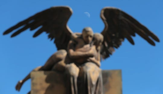 The moon is nestled between the wings of a statue along 16 de Septiembre street in Juarez.