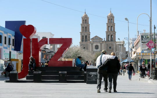 A couple walks arm in arm through downtown Juarez Tuesday, February, 12, 2019. Life has returned to the streets of Juarez after years of cartel killings and extortion kept Juarenses inside their homes.