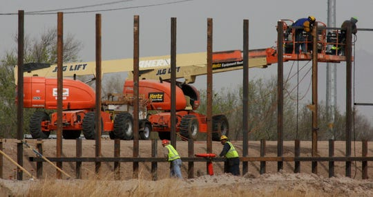 Workers attach supports to the section of the border fence under construction in 2009 near the Azalias Colonia near San Elizario southeast of El Paso. The fence, which has cost millions of dollars, is designed to prevent illegal immigration. While some residents are happy about the fence, others find it unsightly and ineffective.