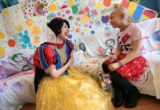 El Paso Children's Hospital oncology patient Bella Ochoa, 8, talks with Snow White during the hospital's seventh birthday celebration Thursday. The children at the hospital created a room of artistic dots to liven up the recreation room at the hospital. Bella shared in the celebration.