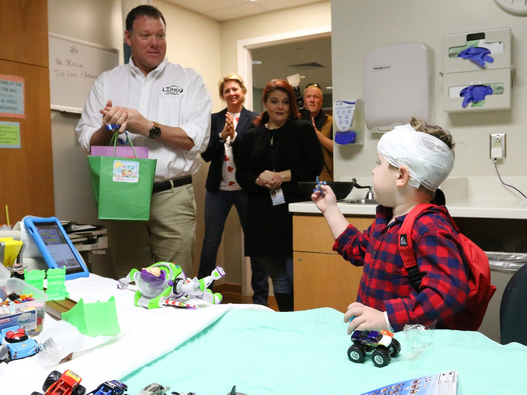 Andy Long, owner and president of Long Heating and Air Conditioning, left, brings Valentine's Day cards to Connor at the Prisma Health Children's Hospital.