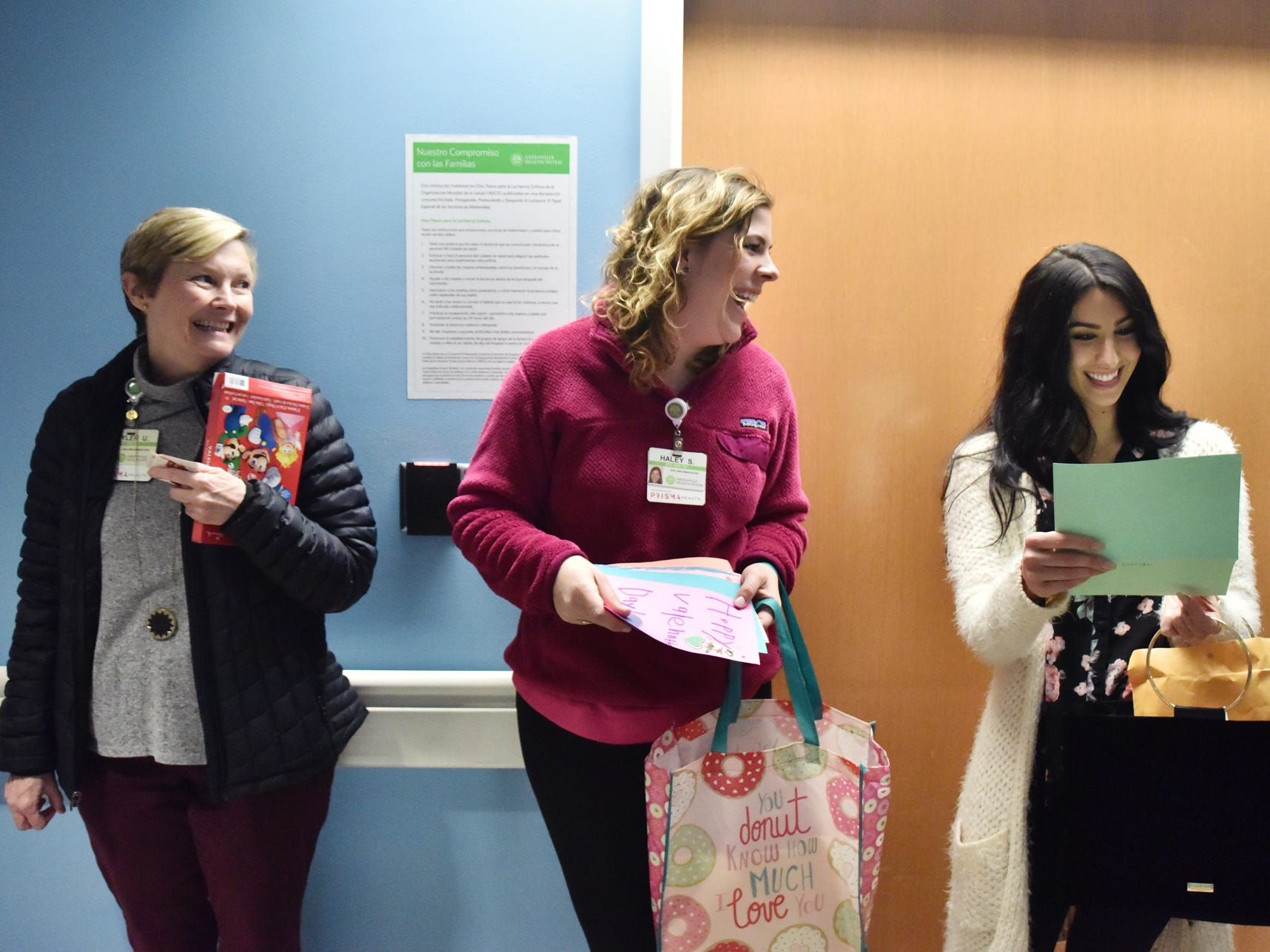 Prisma Health employees laugh together while reading homemade Valentine's Day cards that were made for the children at the Prisma Health Children's Hospital.