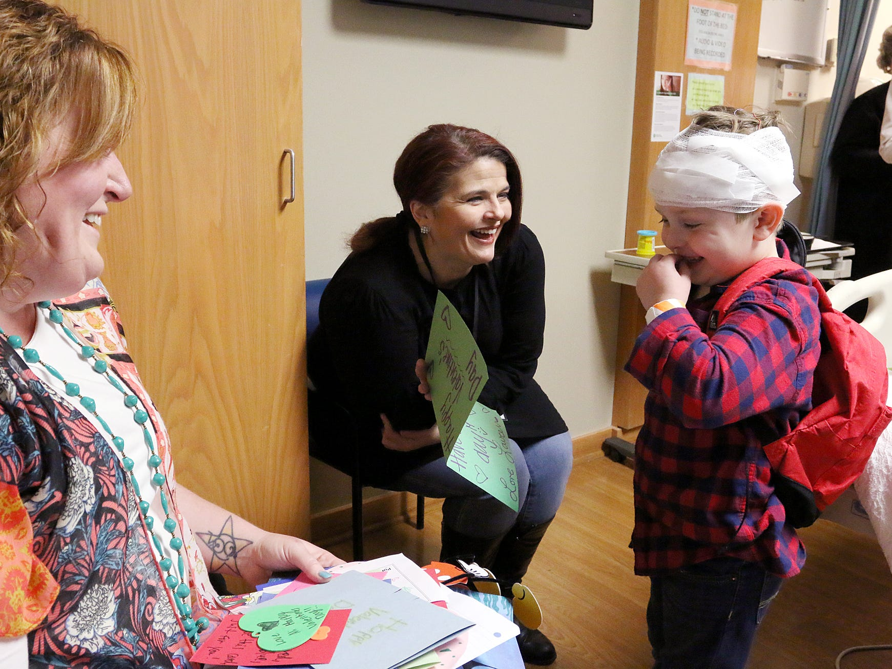 Sheri Taylor, middle, an on-air personality at Magic 98.9, laughs with Connor and his mother Amber Twomey while showing Connor Valentine's Day cards that were made for him and other children at the Prisma Health Children's Hospital Thursday morning, February 14, 2019.
