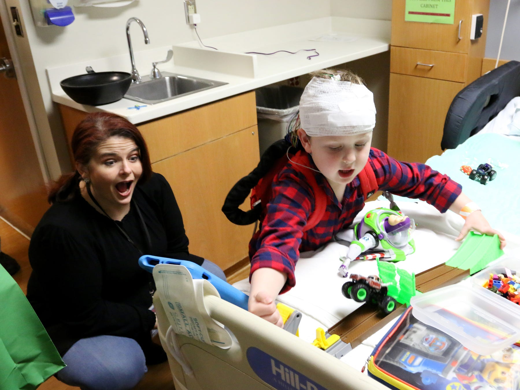 Connor shows his toys to Sheri Taylor, an on-air personality at Magic 98.9, at the Prisma Health Children's Hospital.