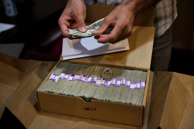 In this June 27, 2017, file photo, the proprietor of a medical marijuana dispensary prepares his monthly tax payment, over $40,000 in cash, at his Los Angeles store.