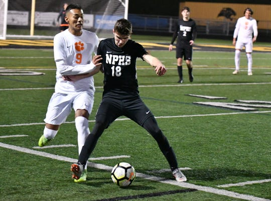 Newbury Park attacker Lukas Locker holds off Riverside Poly's Ron Padilla in Wednesday night's CIF-Southern Section Division 2 quarterfinal at Newbury Park High. Riverside Poly advanced on penalty kicks after a 2-2 tie.