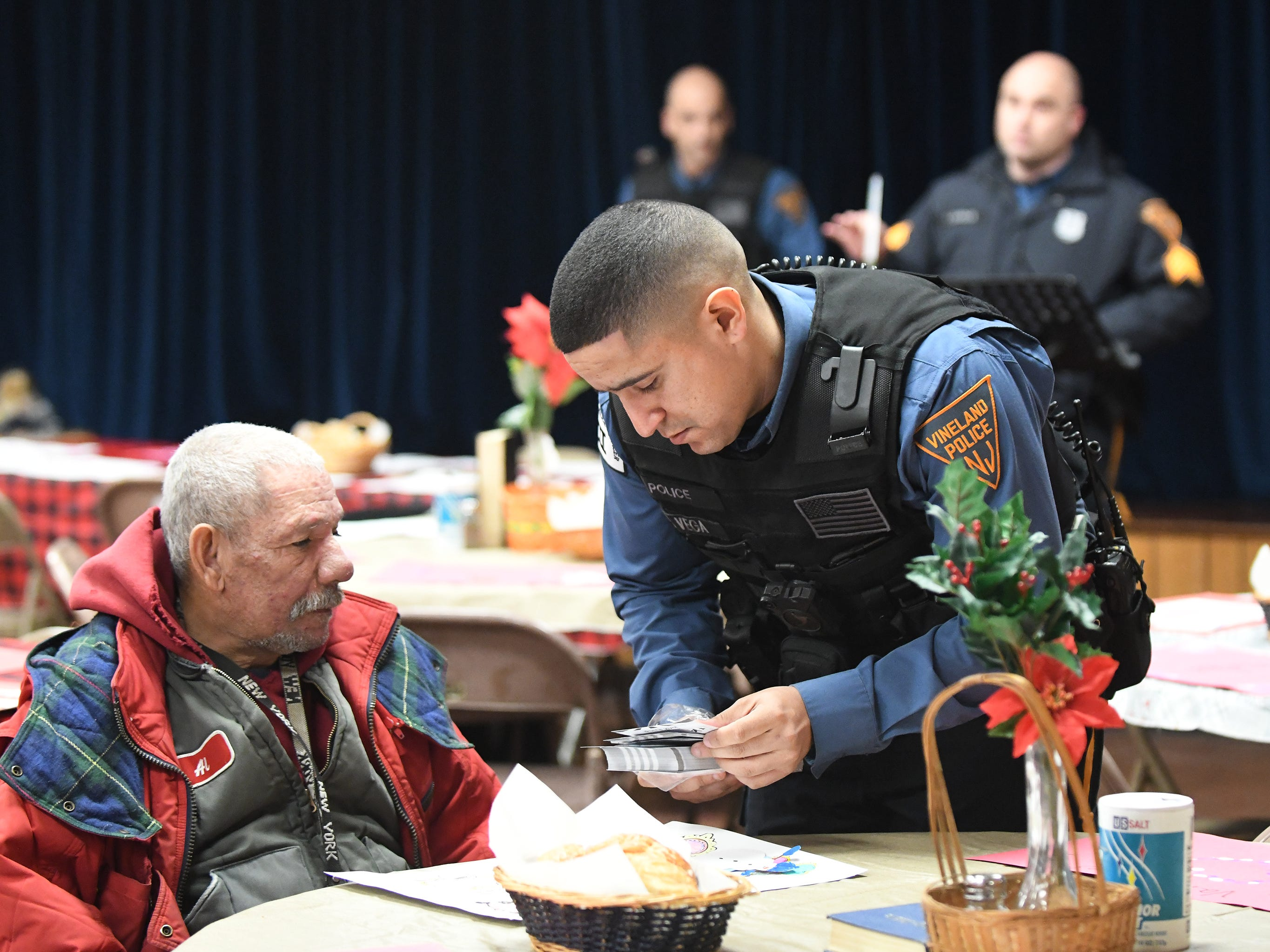 Vineland Police officer Ed Vega hands out pedestrian safety information following a memorial service for Jeffrey Cuss at the Spirit & Truth Ministries Soup Kitchen in Vineland on Thursday, Feb. 14, 2019.