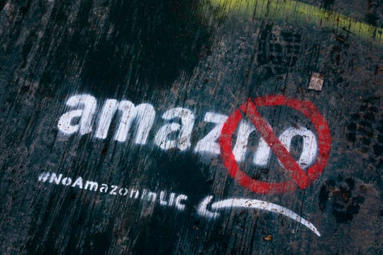 FILE- In this Nov. 16, 2018, file photo graffiti has been painted on a sidewalk by someone opposed to the location of an Amazon headquarters in the Long Island City neighborhood in the Queens borough of New York. Amazon said Thursday, Feb. 14, 2019, that it will not be building a new headquarters in New York, a stunning reversal after a yearlong search. The online retailer has faced opposition from some New York politicians, who were unhappy with the tax incentives Amazon was promised.