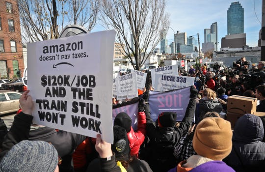 In this Nov. 14, 2018, file photo protesters carry anti-Amazon posters during a coalition rally and press conference opposing Amazon headquarters getting subsidies to locate in the New York neighborhood of Long Island City, Queens in New York.