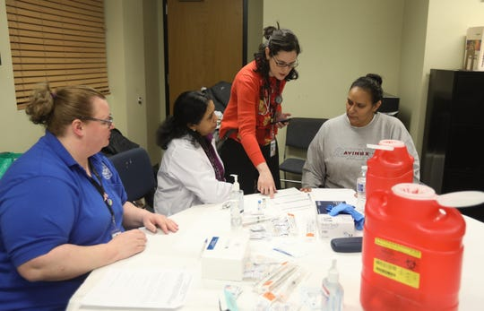 From left, Tonya LaFrancois, Sheela Geevarghese,RN and Dr. Maria Cecilia Mosquera with Rockland Department of Health talk with Terry Rodriguez before giving her a MMR vaccine during a free clinic for residents at the Martin Luther King Multi-Purpose Center in Spring Valley Feb. 13, 2019.