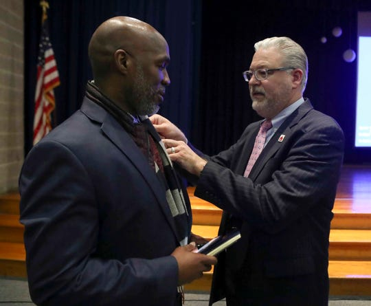 Dorrell Green (left) receives a Red Clay Consolidated School District pin from board member Jason Casper as Casper congratulates him after the board voted him the next superintendent Wednesday.