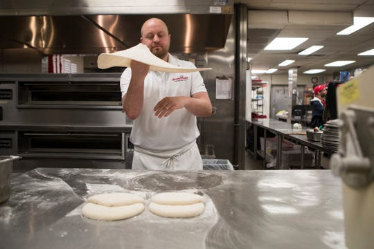 Grotto Pizza's New Castle County Operations Director Russ Wiedenmann shapes dough for a pizza at their Pennsylvania Avenue location.