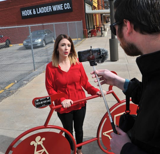 Jana Schmader, executive director of Downtown Wichita Falls Development conducts media interviews after unveiling a new bicycle rack in downtown Thursday morning.