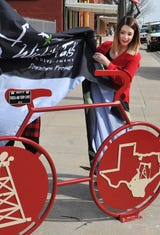 Terry and Teresa Caves, left, along with Jana Schmader, executive director of Downtown Wichita Falls Development unveil the bicycle rack they helped donate. The bike rack is located in downtown Wichita Falls on 7th Street, near Indiana.