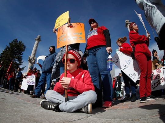 Seven-year-old Emmett Rivera joins his mother and school counselor, Emily, and sister, Lia, during a rally for striking Denver Public Schools instructors in Civic Center Park, Feb. 12, 2019, in Denver.