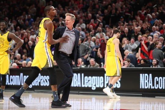 Golden State Warriors forward Kevin Durant holds back head coach Steve Kerr.