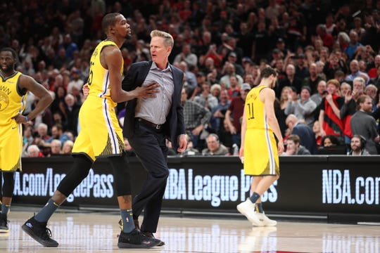 Golden State Warriors forward Kevin Durant holds back head coach Steve Kerr.