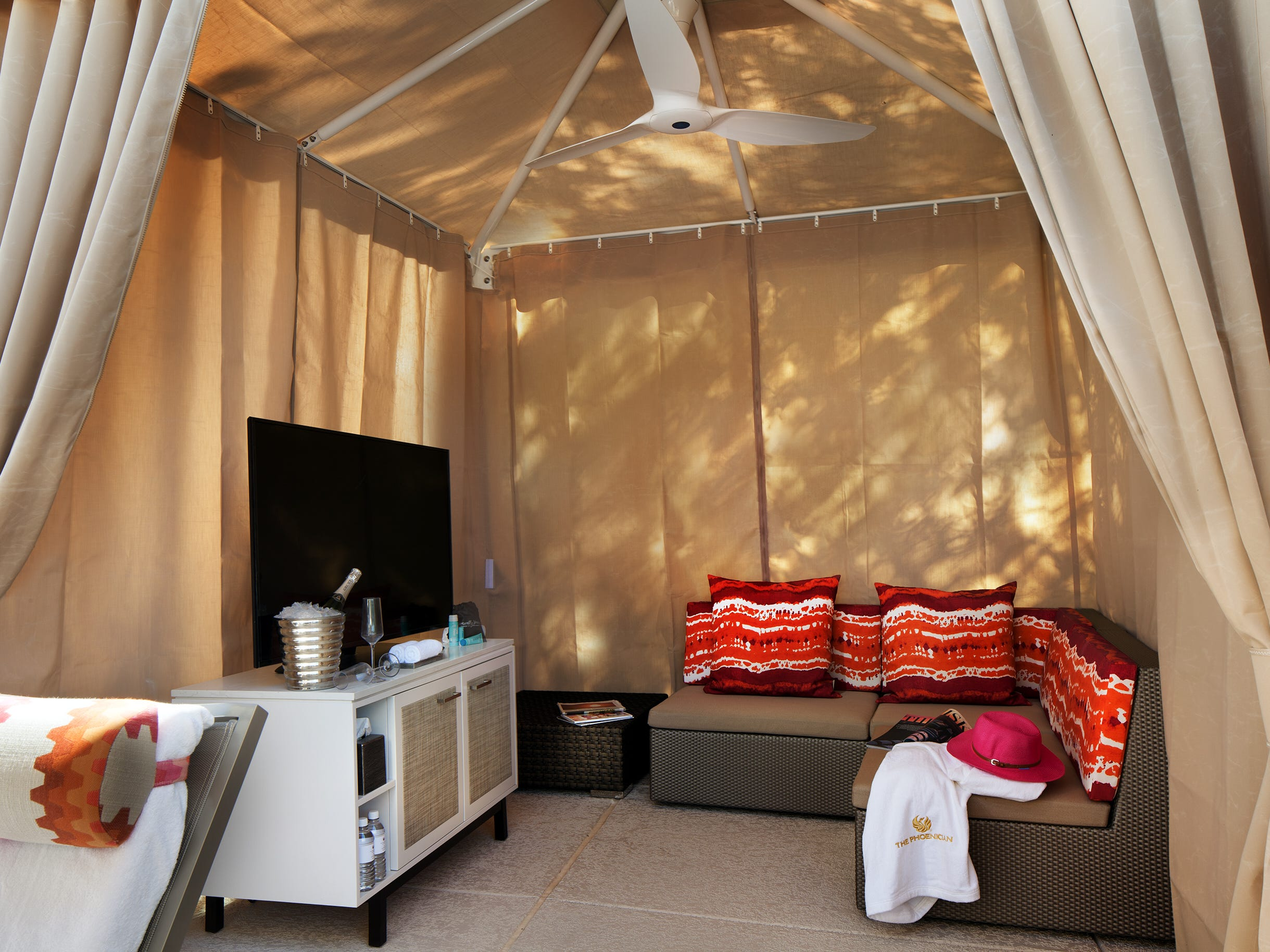 A cozy poolside cabana at The Phoenician in Phoenix comes with a flat-screen TV, couch, bottled water and a choice of snack, including guacamole. Champagne is optional. The cabanas range from $250 to $450 a day depending on location, season and day of the week.