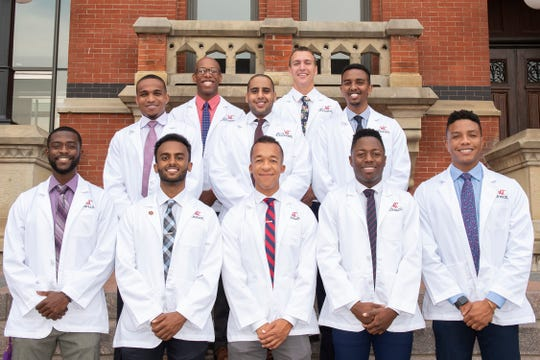 "These are the 10 black men in University of Cincinnati College of Medicine's first year class at their ""White Coat Ceremony,"""