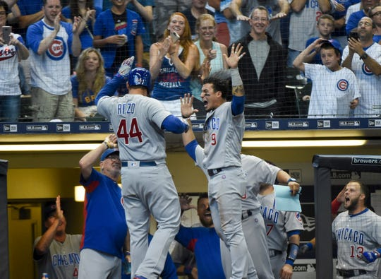Chicago Cubs first baseman Anthony Rizzo is greeted  by third baseman Javier Baez (9) after hitting a homer against the Milwaukee Brewers at Miller Park.