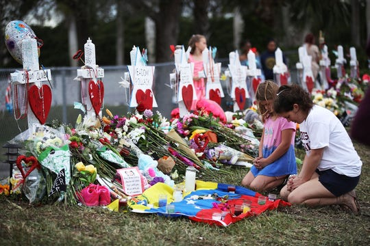 People visit a makeshift memorial set up in front of Marjory Stoneman Douglas High School on Feb. 19, 2018, in Parkland, Florida.