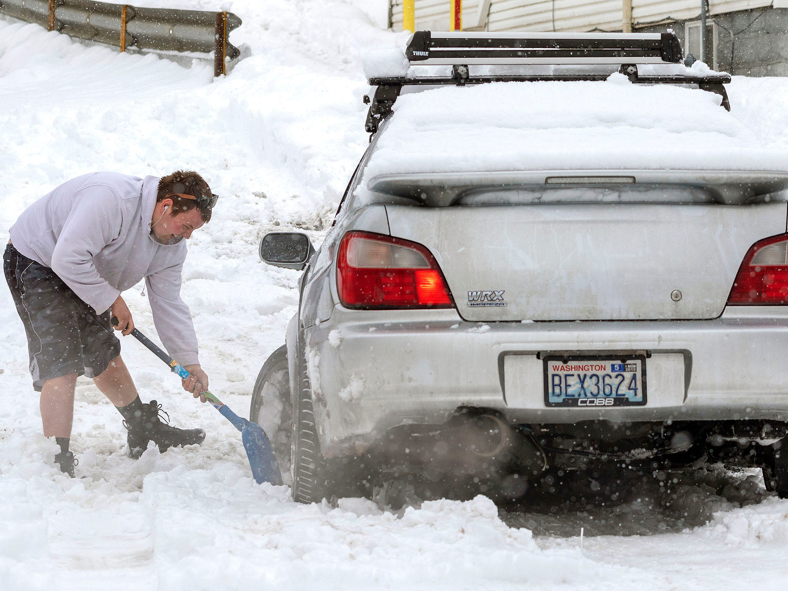 A motorist works to get his stuck car out of his driveway on Feb. 13, 2019, during a snow storm in Pullman, Wash.
