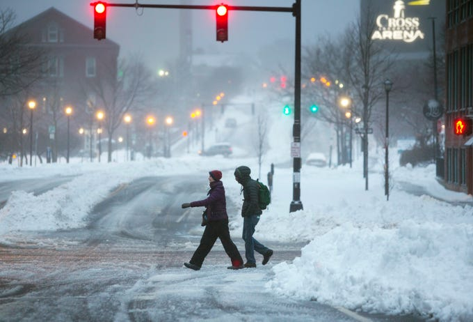 Pedestrians cross an intersection in Portland, Maine on Feb. 13, 2019.