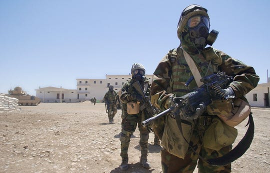 US Army soldiers wearing full chemical protection suits walk inside the courtyard of an industrial complex they secured which they thought was a possible site for weapons of mass destruction in the central Iraqi town of Baquba in May 2003. The building, which was used as a bread factory, was secured without any incidents and no WMD were found.