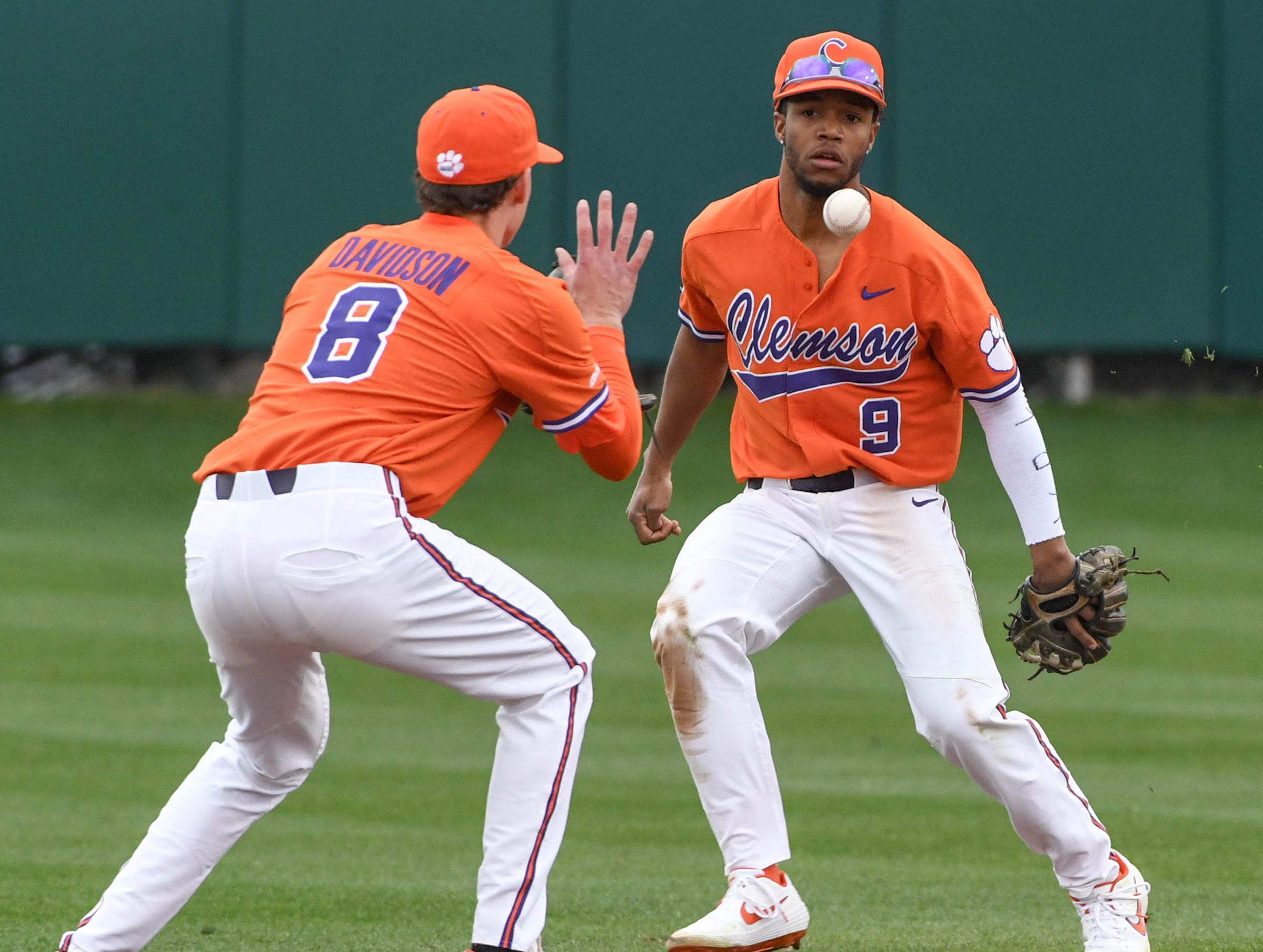 Clemson infielder Jordan Greene(9) flips a ball to teammate junior Logan Davidson(8) to make a play at first against South Alabama during the top of the fourth inning at Doug Kingsmore Stadium in Clemson Friday, February 15, 2019.