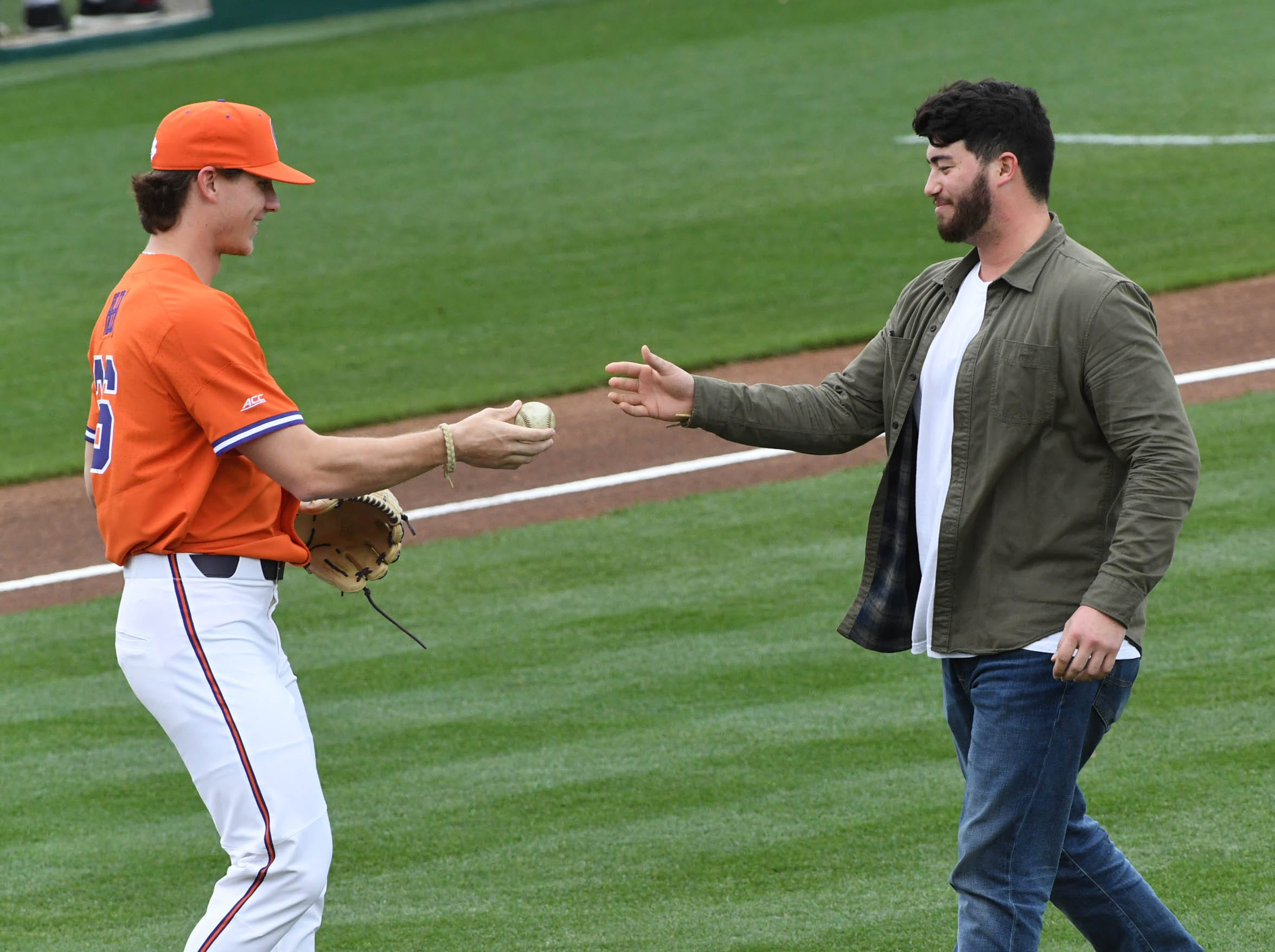 Clemson junior Sheldon Reed(36) gives former Clemson baseball player Chris Williams the ceremonial first pitch ball before the game at Doug Kingsmore Stadium in Clemson Friday, February 15, 2019.
