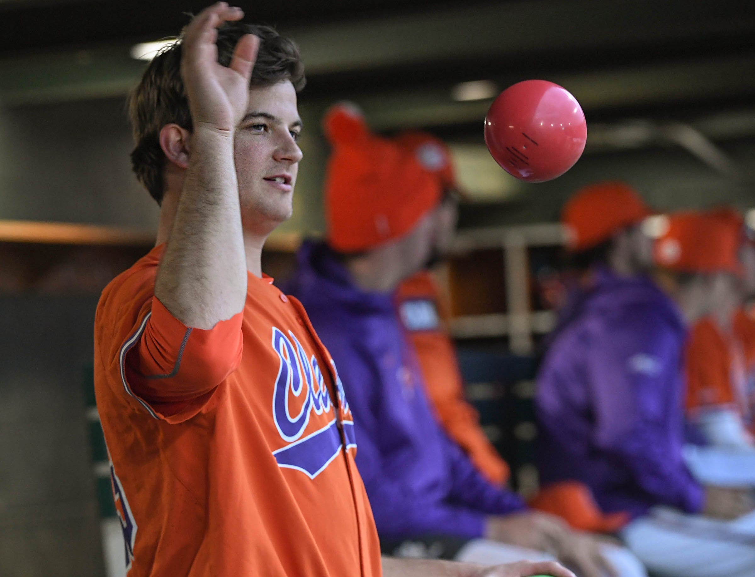 Clemson junior Carson Spiers(23) tosses exercise balls in the dugout between pitching innings against South Alabama during the top of the eighth inning at Doug Kingsmore Stadium in Clemson Friday, February 15, 2019.