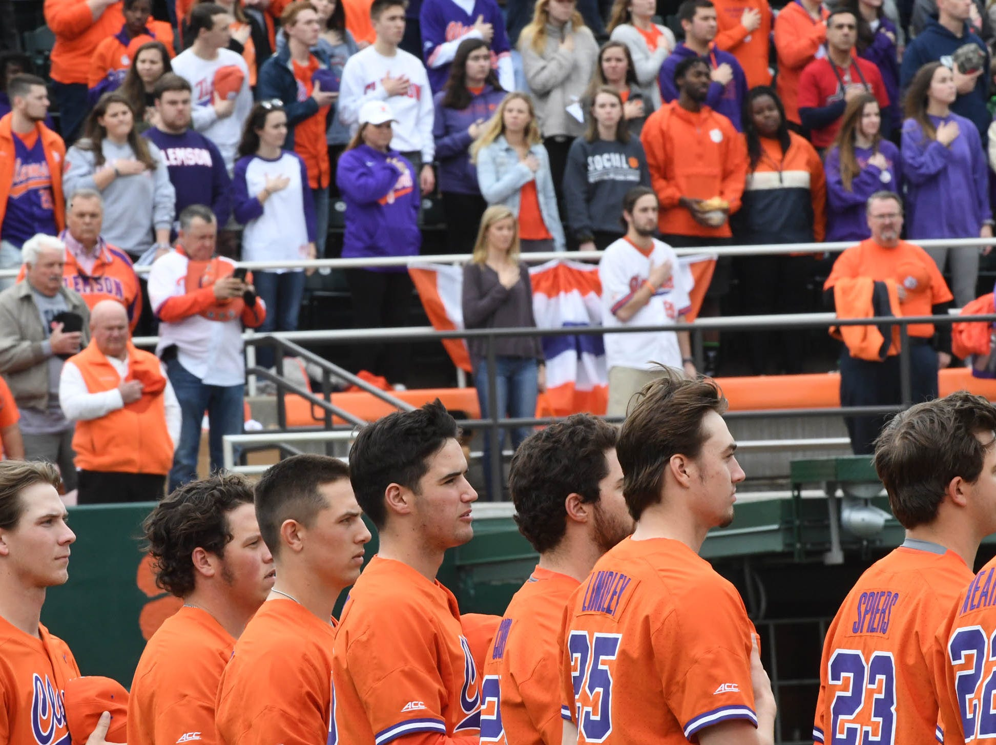 Clemson players and fans join in the National Anthem before the first inning at Doug Kingsmore Stadium in Clemson Friday, February 15, 2019.