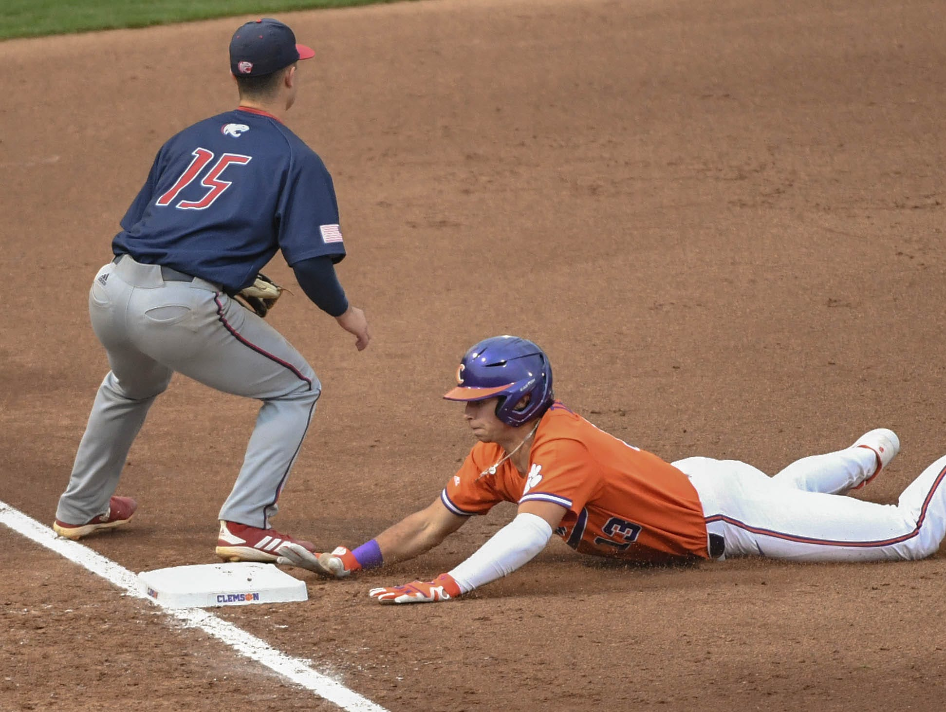 Clemson sophomore Bryce Teodosio(13) advances to third base near South Alabama infielder Kaleb DeLaTorre (15) during the bottom of the eighth inning at Doug Kingsmore Stadium in Clemson Friday, February 15, 2019.
