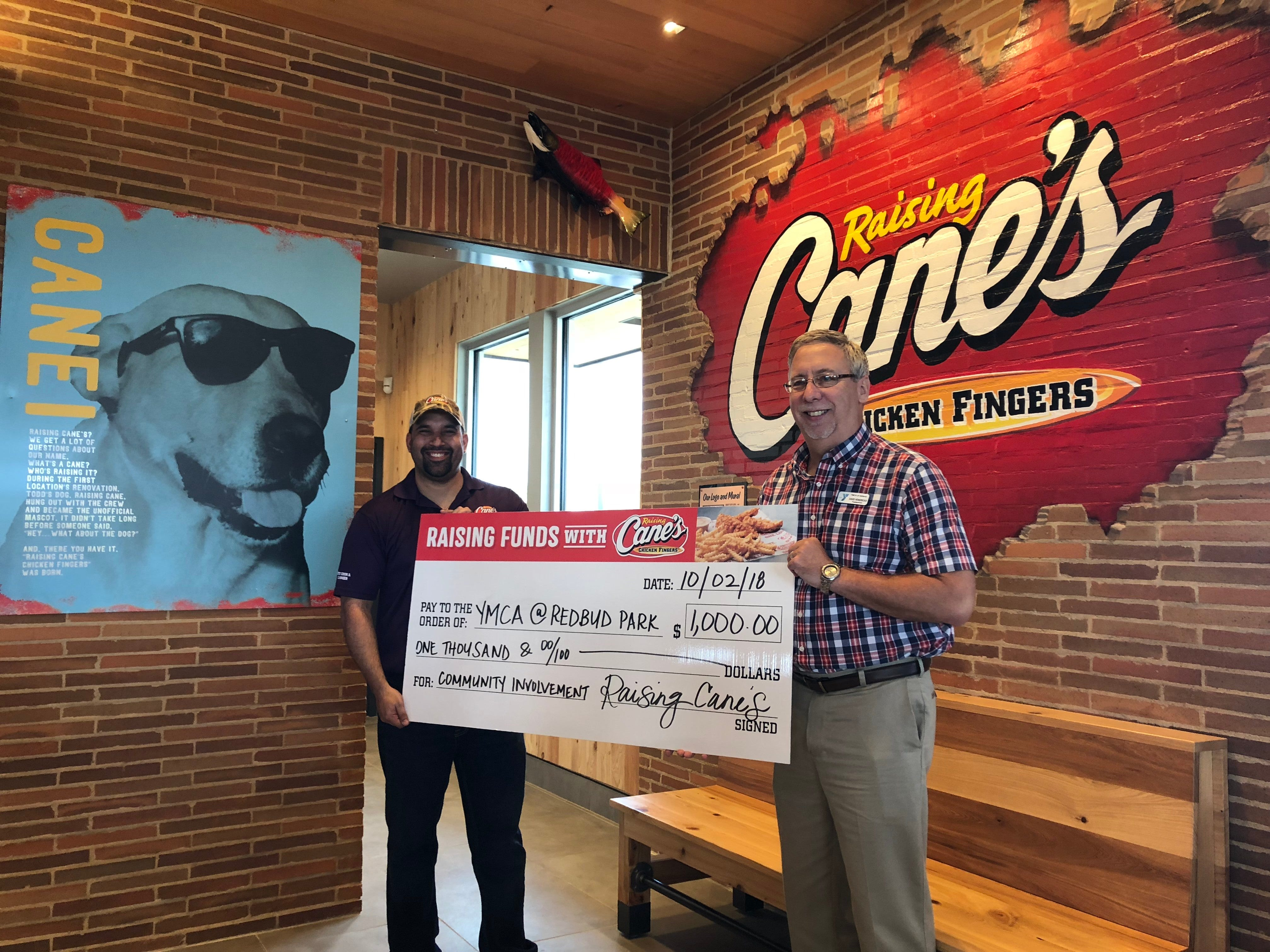 Ricky Merced, general manager of the new Raising Cane's location in south Abilene, presents a $1,000 donation to David Hendricks, president and CEO of the YMCA of Abilene.
