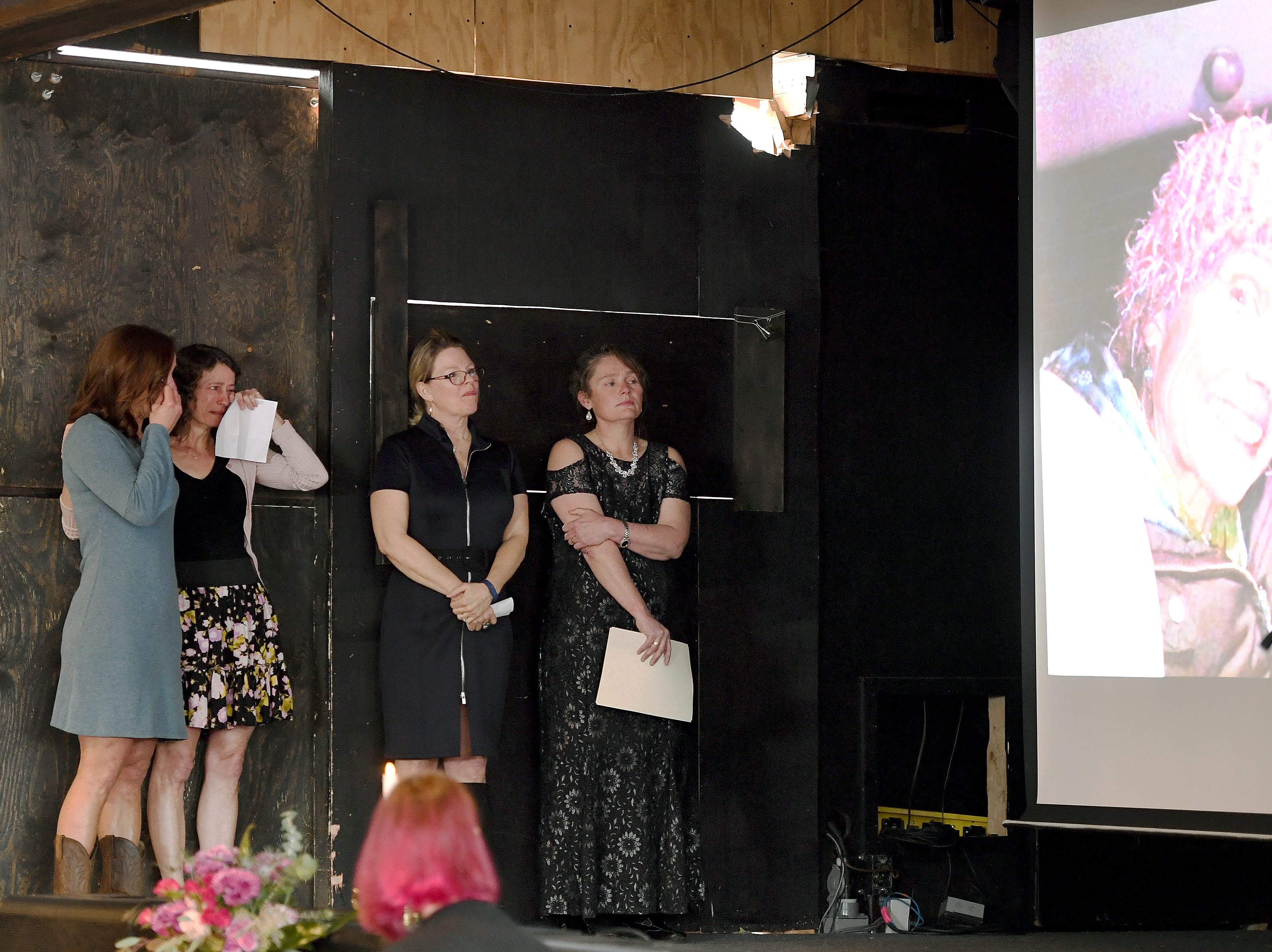 "Close friends of Karen Shuart, Kelley Klope, Anne Squires, Skye Myrick and Joy Ponder comfort each other as they watch a photo slideshow during a memorial service at the Salvage Station on Feb. 15, 2019 for the firefighter who died of cancer last month. Shuart died of cancer, the second cancer-related death in the department in a year. Her death is being considered an ""line-of-duty"" death."