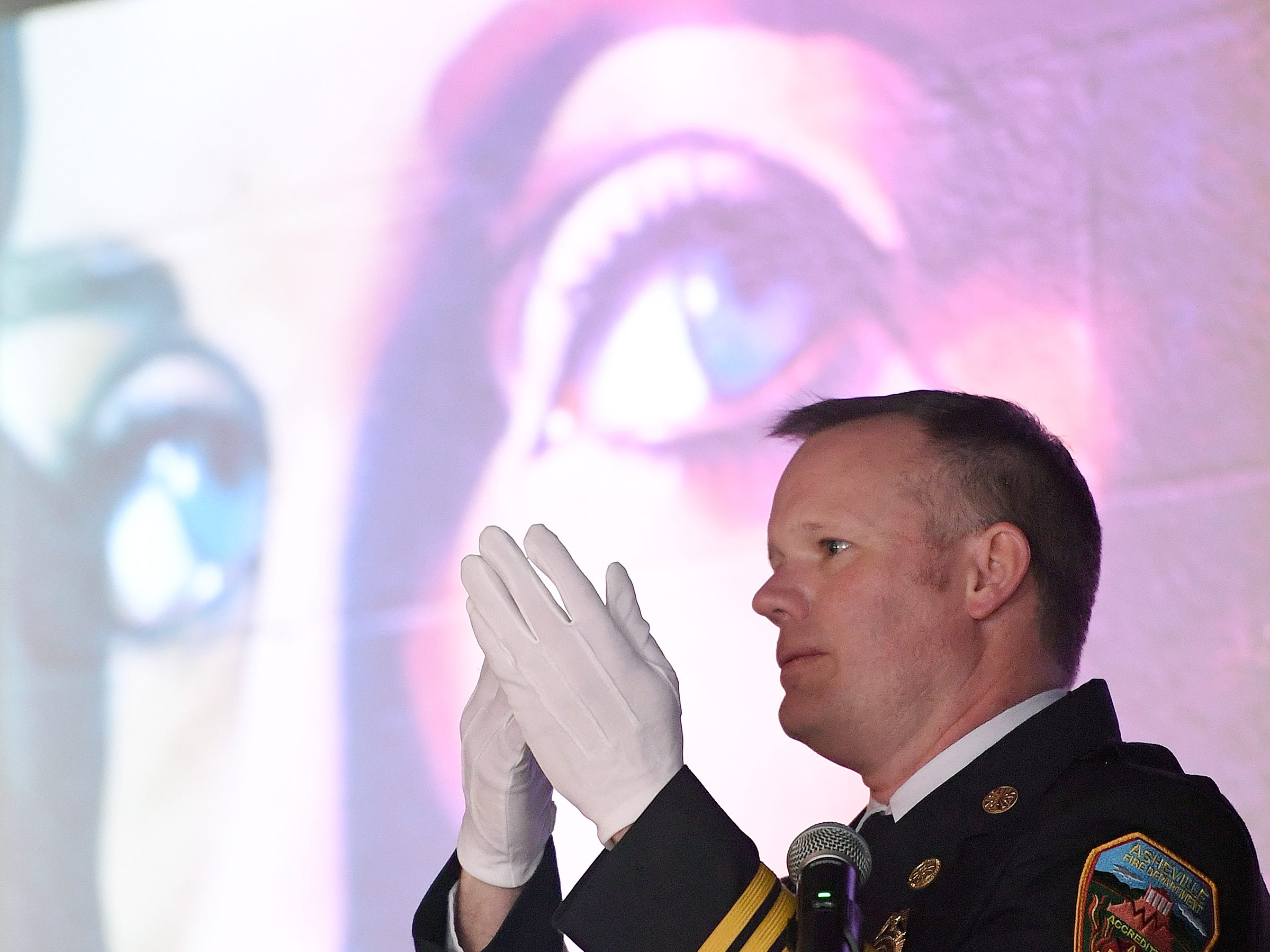 "Asheville Fire Chief Scott Burnette makes the American Sign Language sign for ""grateful"" a word he said Karen Shuart used to sign her emails during a memorial service at the Salvage Station on Feb. 15, 2019 for the firefighter who died of cancer last month. Shuart used ASL to communicate with her parents."