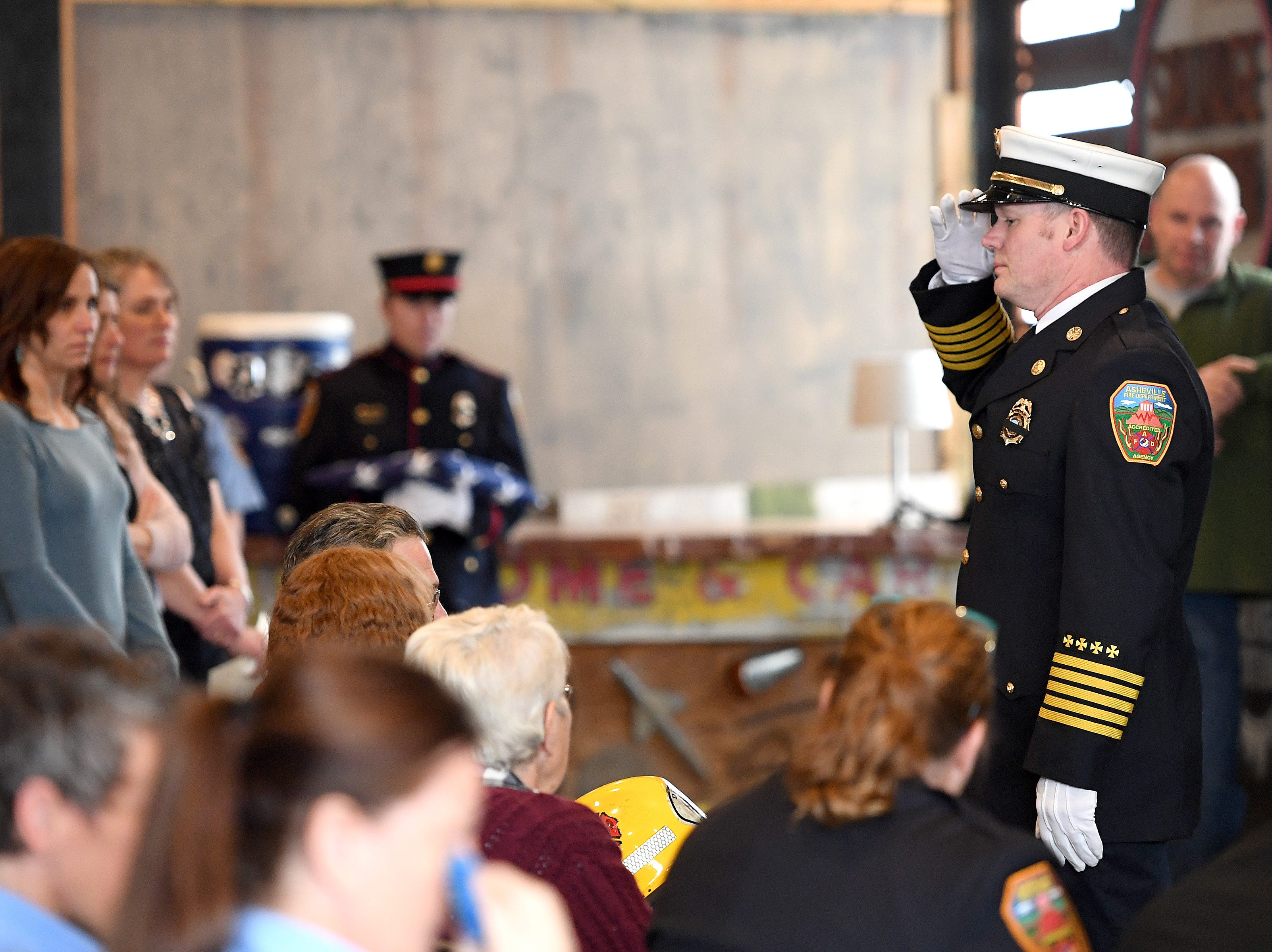 "Asheville Fire Chief Scott Burnette presents Karen Shuart's helmet to her family during a memorial service at the Salvage Station on Feb. 15, 2019 for the firefighter who died of cancer last month. Shuart died of cancer, the second cancer-related death in the department in a year. Her death is being considered an ""line-of-duty"" death."