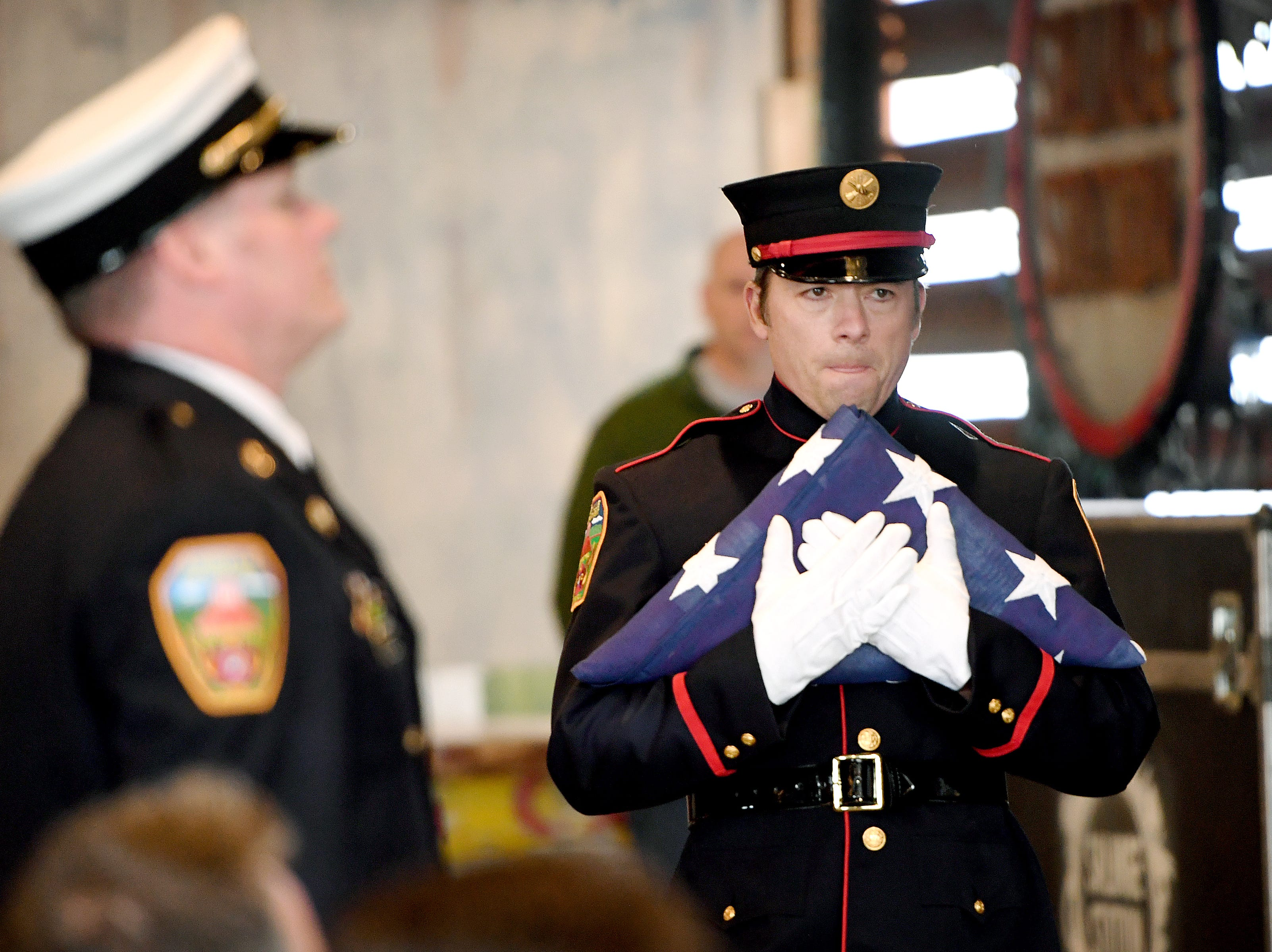 "Neil Spencer, with the Asheville Fire Department honor guard, carries a flag to Fire Chief Scott Burnette so they can present it to the family of Karen Shuart's during a memorial service at the Salvage Station on Feb. 15, 2019 for the firefighter who died of cancer last month. Shuart died of cancer, the second cancer-related death in the department in a year. Her death is being considered an ""line-of-duty"" death."